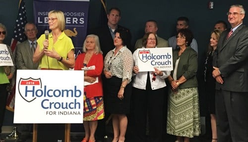 (Image courtesy of Eric Holcomb's Twitter account) Suzanne Crouch is pictured at the podium and Eric Holcomb is pictured far-right.