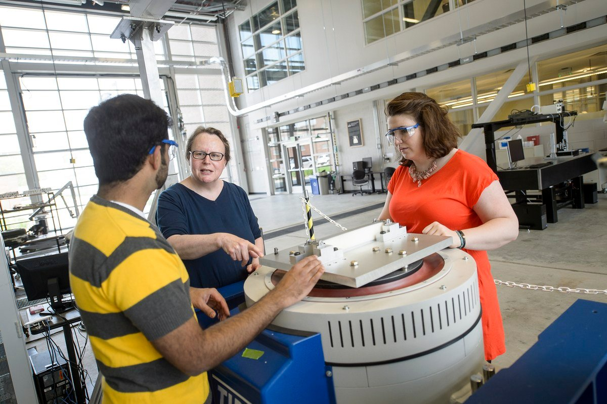 A Purdue professor and graduate students prepare a vibration experiment; the work will help build car seat models to optimize comfort and vibration isolation.