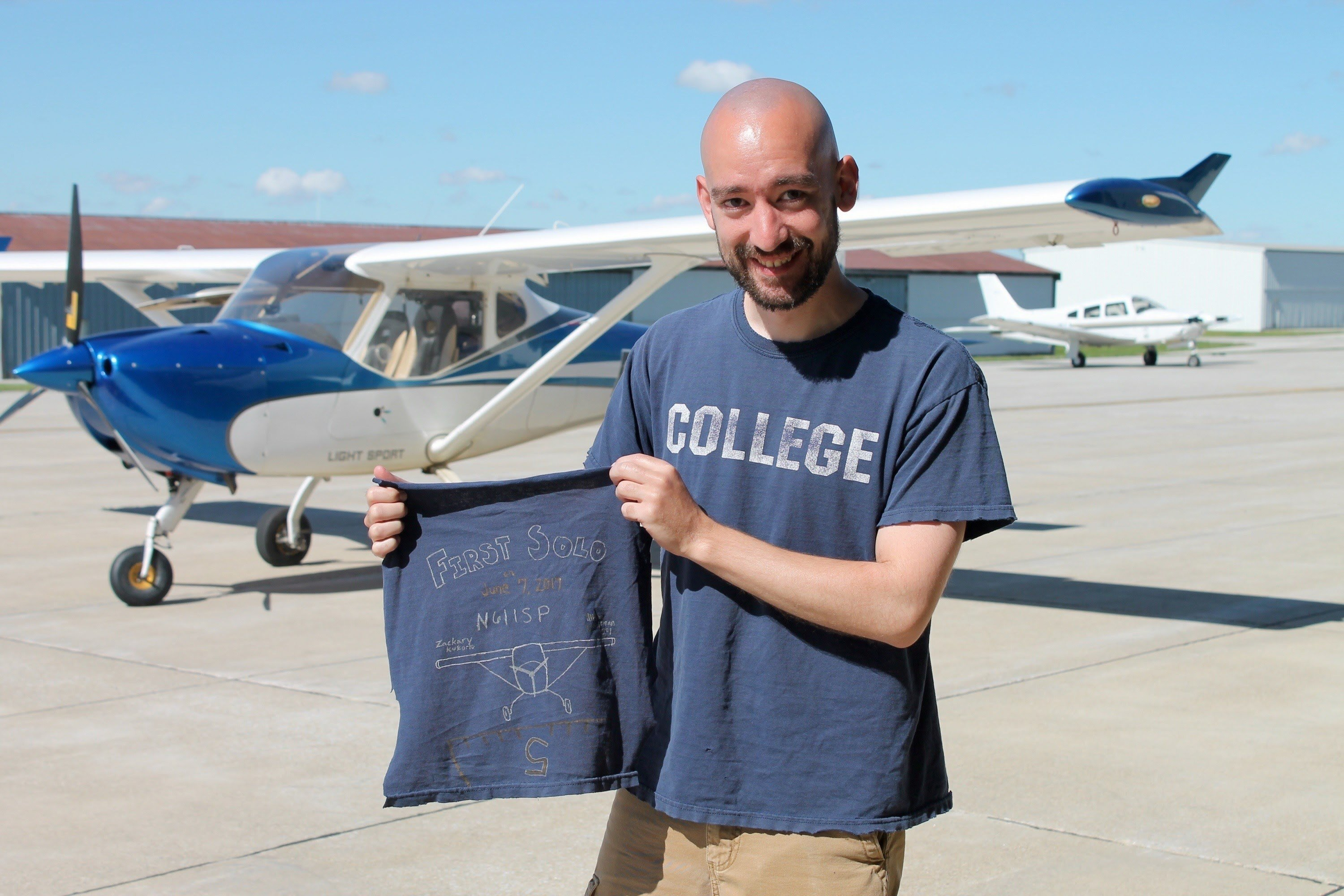 """Following tradition, Kukorlo cut his """"tail"""" (the back of his shirt) for his first solo flight."""