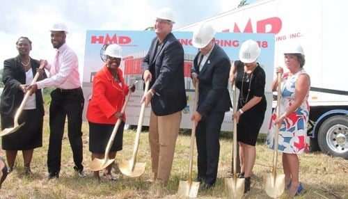 Gary Mayor Karen Freeman-Wilson (wearing red in center) and Governor Eric Holcomb (pictured to Freeman-Wilson's left) were on-hand for a groundbreaking at the future site of the new HMD Trucking headquarters.