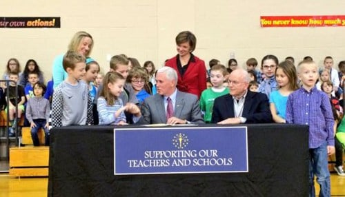 Pence signed the bill surrounded by students and teachers from Eagle Elementary School in Zionsville.