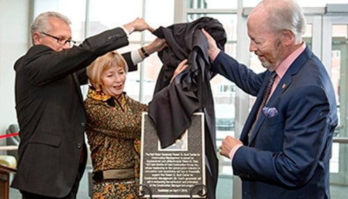 Ball State Acting President Terry King (left) assists Diane and Robert G. Hunt with the unveiling of a plaque recognizing the couple's support.