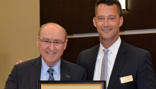 Pictured with Purdue Board of Trustees Chair Michael Berghoff (right), retiring Purdue University North Central Chancellor James Dworkin holds a Resolution of Appreciation he received from university trustees.