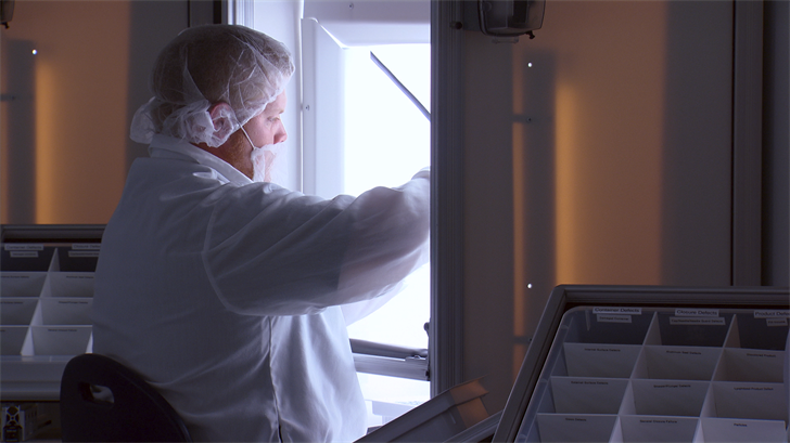 A Catalent employee inspects a vial.