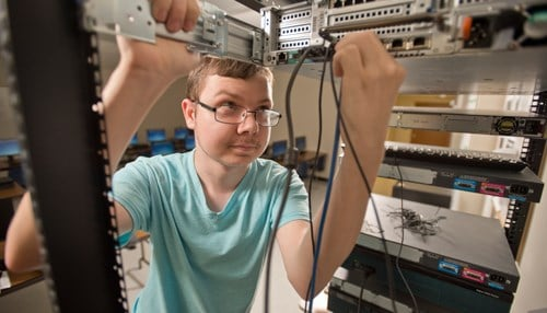 A computer science undergrad at Trine University is working on servers in the computer lab