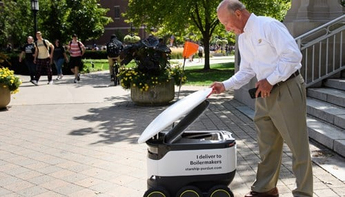 Purdue Pres. Mitch Daniels receives his delivery from a robot. (photo courtesy: Purdue)